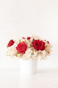 Verticale opname van een mooi boeket met rode rozen en leliebloemen in een doos