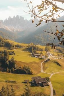 Verticale opname van een mooi dorp op een heuvel, omringd door bergen bij daglicht