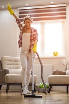 Verticale opname van een mooie blanke vrouw die het huis schoonmaakt en plezier heeft