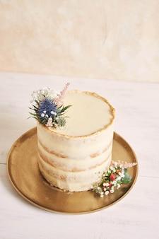 Verticale opname van een mooie en heerlijke cake met bloem en gouden randen op een witte achtergrond