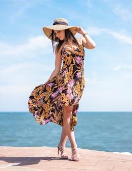Verticale opname van een mooie vrouw in een bloemenzomerjurk en een hoed aan de prachtige zee in spanje
