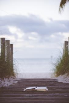 Verticale opname van een open bijbel op een houten pad naar de zee met een onscherpe achtergrond