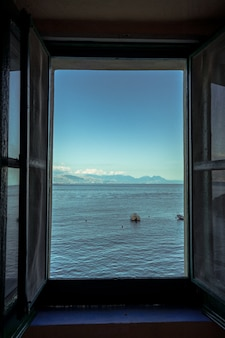Verticale opname van een open raam met uitzicht op de prachtige zee