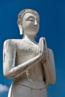 Verticale opname van een oud boeddhabeeld met een heldere blauwe hemel