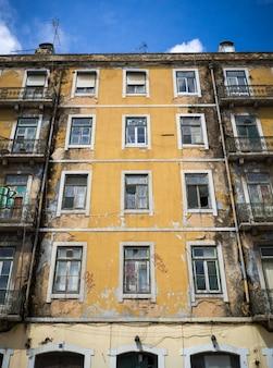 Verticale opname van een oud geel geverfd flatgebouw met enkele gebroken ramen