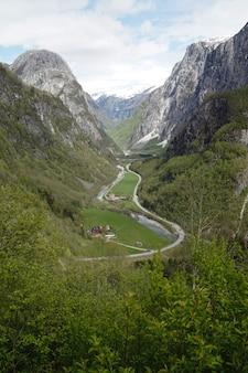 Verticale opname van een pad door bergen met groene velden
