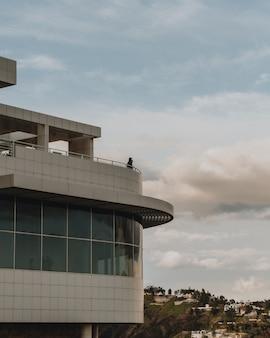Verticale opname van een persoon die bovenop het gebouw staat