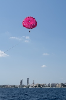 Verticale opname van een persoon die parachutespringt over de zee in de buurt van de stad