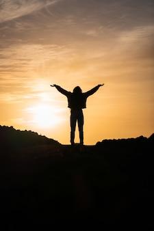 Verticale opname van een persoon met de handen omhoog tegen de achtergrond van de zonsondergang