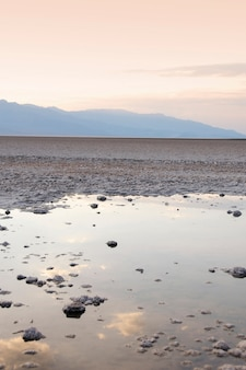 Verticale opname van een plas gevuld met veel rotsen met de weerspiegeling van de zonsondergang