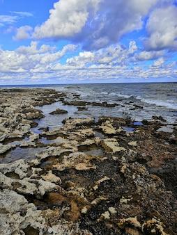 Verticale opname van een prachtig rotsachtig strand in malta, vastgelegd op een zonnige dag