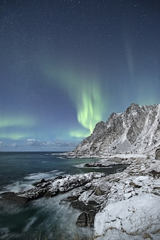 Verticale opname van een prachtige besneeuwde klif aan zee met het noorderlicht aan de hemel