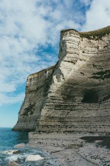 Verticale opname van een prachtige rotsachtige klif aan de rustige zee overdag