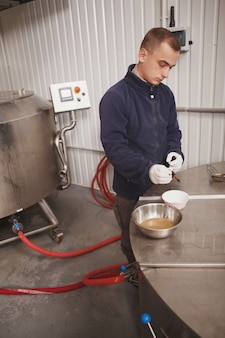 Verticale opname van een professionele brouwer die bier test, die bij microbrouwerij werkt