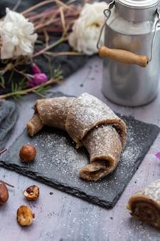 Verticale opname van een rauw veganistisch broodje gemaakt van hazelnoten op een paarse grunge tafelblad