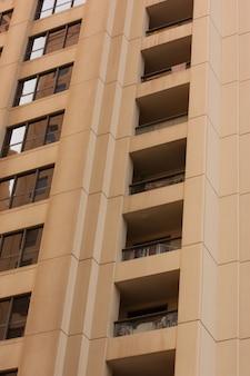 Verticale opname van een roze hoog gebouw met balkons en glazen ramen