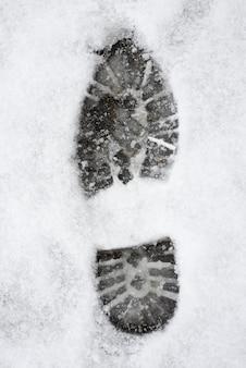 Verticale opname van een schoenafdruk op een witte besneeuwde ondergrond