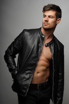 Verticale opname van een sexy topless man in leren jas poseren over grijze achtergrond