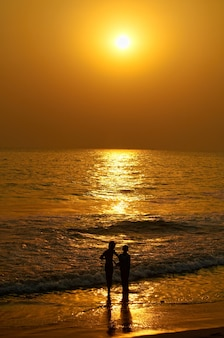 Verticale opname van een silhouet van een stel op het strand