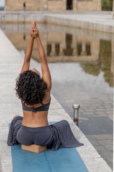 Verticale opname van een spaanse vrouw die buiten yoga beoefent