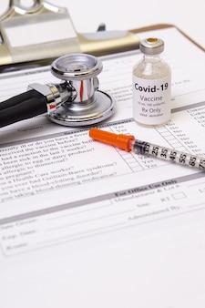 Verticale opname van een stethoscoop, een medicijn en een spuit op een gedrukt papier