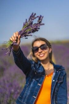 Verticale opname van een stijlvolle dame in een lavendelveld