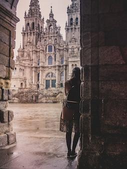 Verticale opname van een stijlvolle vrouw in de kathedraal van santiago de compostela in spanje op een regenachtige dag