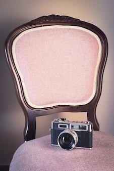 Verticale opname van een stoel met een vintage fotocamera erop