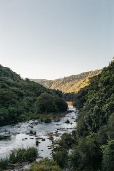 Verticale opname van een stromende rivier, omringd door bergen met een heldere hemel