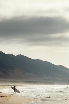 Verticale opname van een surfer op een strand van cofete, fuerteventura, canarische eilanden
