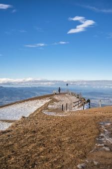 Verticale opname van een uitkijkplatform met uitzicht op een stadsvallei met blauwe lucht