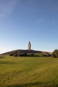 Verticale opname van een veld met de toren van hercules in de verte in coruna, spanje