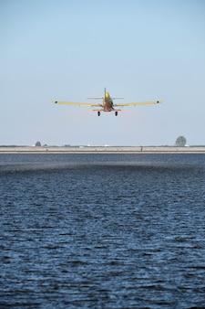 Verticale opname van een vintage eenmotorig vliegtuig met een propeller die over een boerderijlandschap vliegt