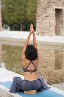 Verticale opname van een vrouw die buiten yoga beoefent