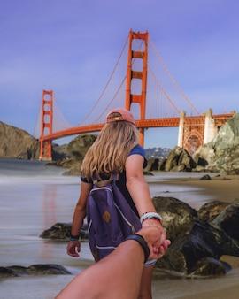 Verticale opname van een vrouw die de hand van een man vasthoudt en hem naar de golden gate bridge leidt