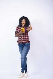 Verticale opname van een vrouw die haar telefoon gebruikt en een duim omhoog steekt