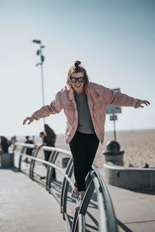 Verticale opname van een vrouw die lachend over het hek loopt