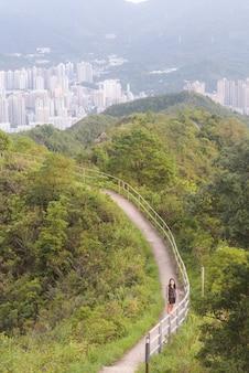 Verticale opname van een vrouw die op een smal pad loopt, omringd door bomen en groen