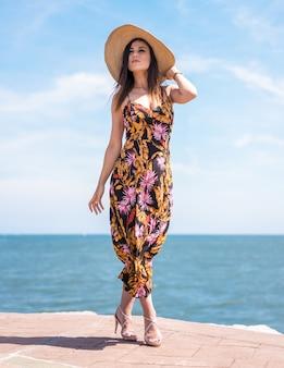Verticale opname van een vrouw in gebloemde jurk en hoed gevangen door de oceaan in san sebastian, spanje