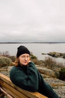 Verticale opname van een vrouw zittend op een houten bank met een zelfvoldane blik terwijl ze kijkt