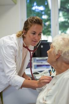 Verticale opname van een vrouwelijke arts die luistert naar een oudere hartslag