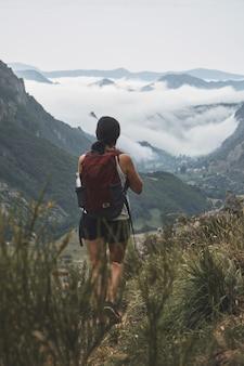 Verticale opname van een vrouwelijke backpacker die naar wolken kijkt die de vallei in het natuurpark somiedo bedekken