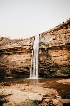Verticale opname van een waterval die overdag van een lage klif in een klein grasveld stroomt