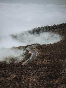 Verticale opname van een weg die door mistige landschappen leidt