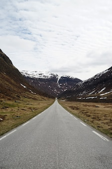 Verticale opname van een weg die leidt naar prachtige besneeuwde bergen