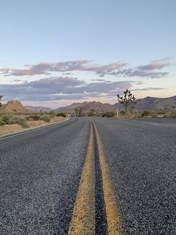 Verticale opname van een weg door heuvels en bergen tijdens zonsondergang