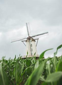Verticale opname van een windmolen met een bewolkte grijze lucht
