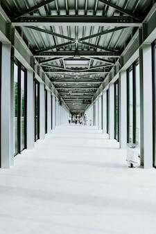 Verticale opname van een witte gang met glazen deuren en een metalen plafond in een modern gebouw