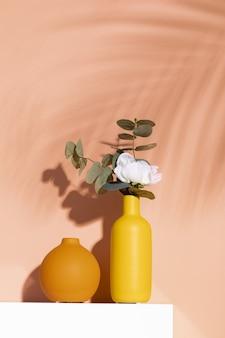 Verticale opname van een witte roos in een decoratieve gele vaas tegen een oranje muur