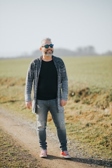 Verticale opname van een zelfverzekerde man met grijs haar die lacht en opzij kijkt op de achtergrond van het veld